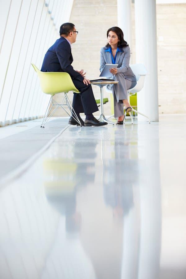 Geschäftsmann-und Geschäftsfrau-Sitzung im modernen Büro stockfotografie