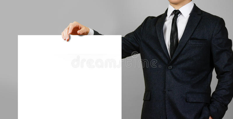 Geschäftsmann und leeres großes weißes Brett auf grauem backgrou lizenzfreie stockfotografie