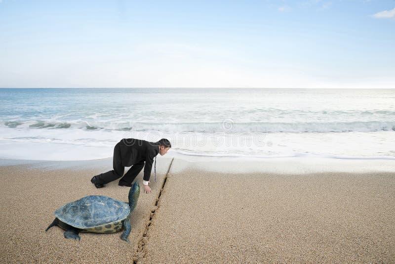 Geschäftsmann und Schildkröte sind bereit, auf Sandstrand zu laufen lizenzfreies stockbild