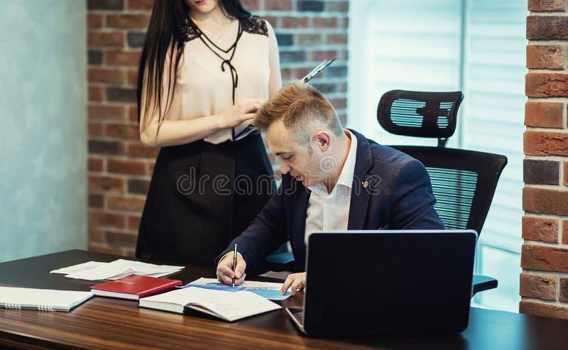 Geschäftsmann und sein behilflicher Sekretär in seinem Büro Das Secre lizenzfreie stockfotografie