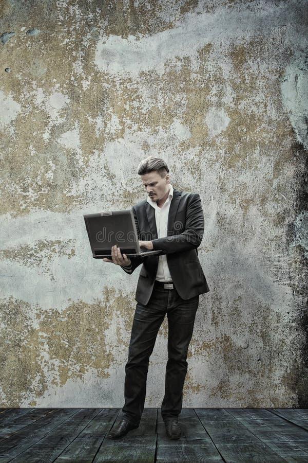 Geschäftsmann und sein Laptop lizenzfreie stockbilder