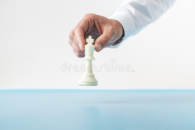 Geschäftsmann ungefähr, zum einer Königschachzahl auf einem Blau zu setzen lizenzfreies stockbild