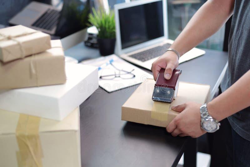 Geschäftsmann unter Verwendung der Metallbandzufuhr und -c$verpackens eines Paketkastens auf schwarzem Schreibtisch im Innenminis stockfotografie
