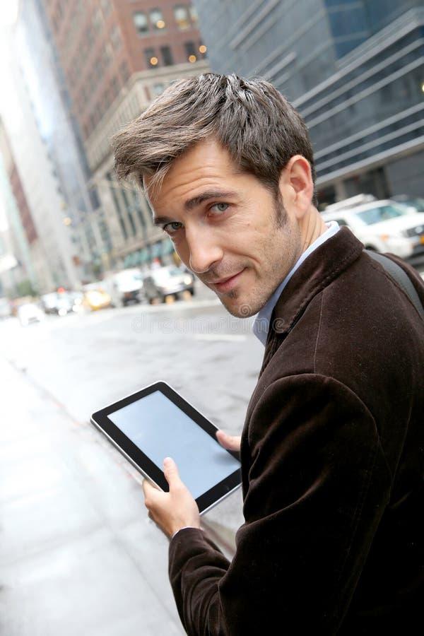 Geschäftsmann unter Verwendung der Tablette in den Straßen stockfoto