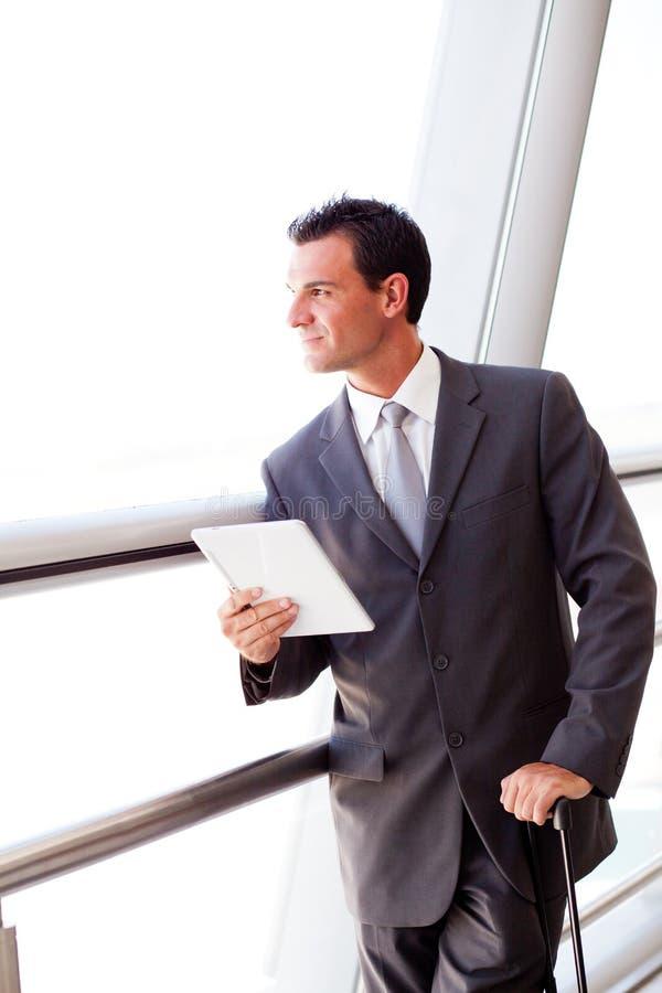 Geschäftsmann unter Verwendung der Tablette am Flughafen stockfotos