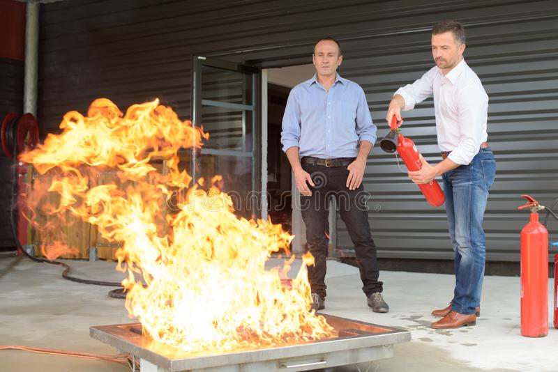 Geschäftsmann unter Verwendung des Feuerlöschers während des Feuertrainings lizenzfreies stockbild