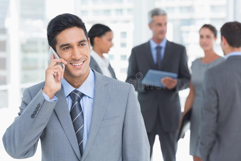 Geschäftsmann unter Verwendung des Handys mit Kollegen hinten lizenzfreies stockbild