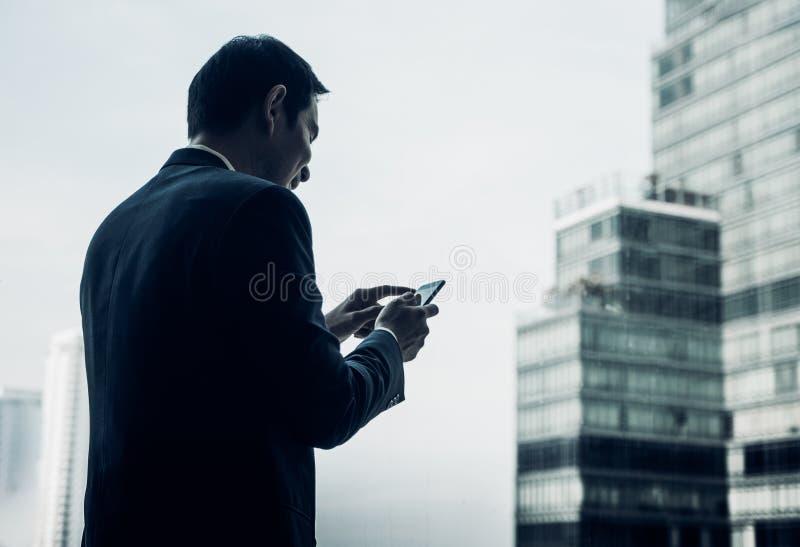 Geschäftsmann unter Verwendung des Handys nahe Bürofenster an Büro buil lizenzfreies stockfoto