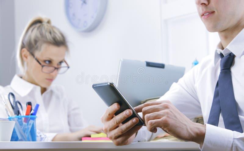 Geschäftsmann unter Verwendung des intelligenten Telefons im Büro stockfoto