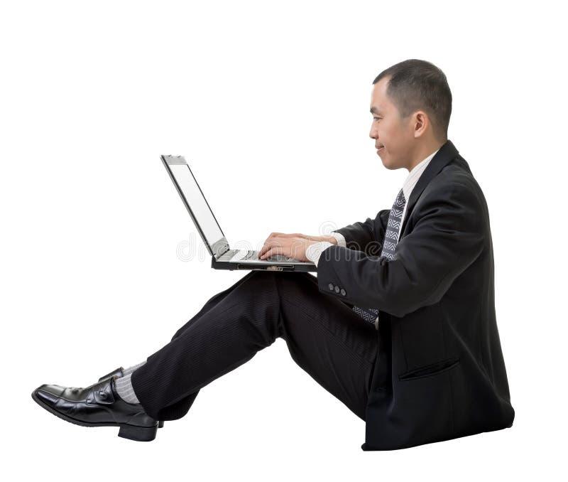 Geschäftsmann unter Verwendung des Laptops auf dem Boden stockfotografie