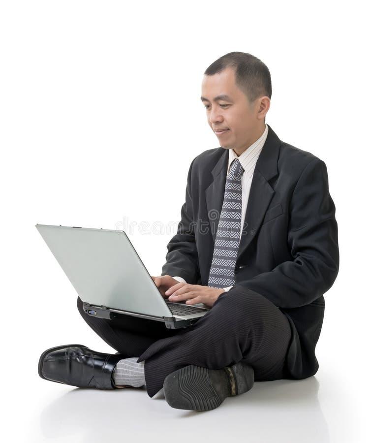 Geschäftsmann unter Verwendung des Laptops auf dem Boden lizenzfreie stockbilder