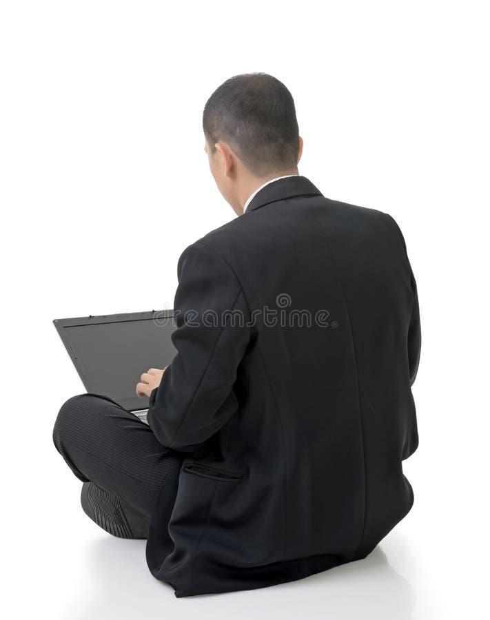 Geschäftsmann unter Verwendung des Laptops auf dem Boden stockbild