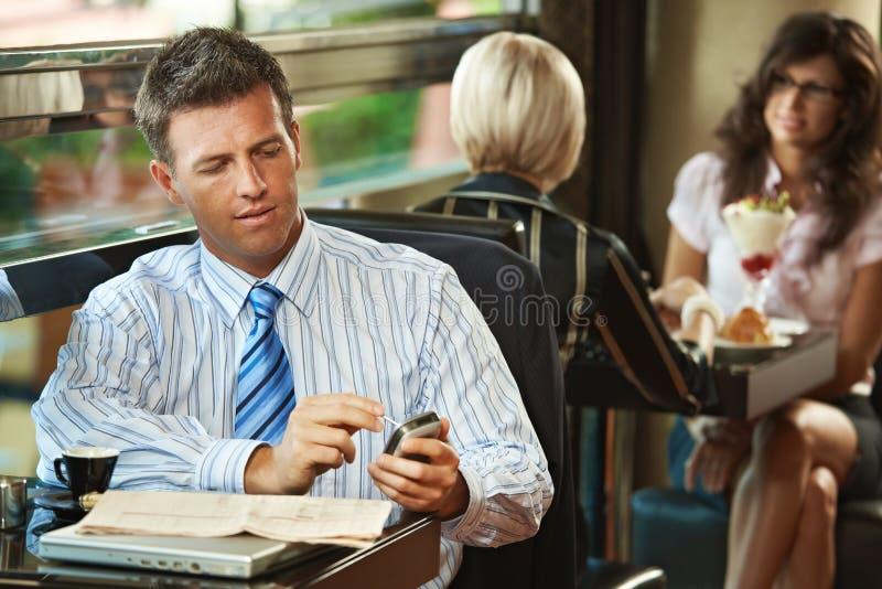 Geschäftsmann unter Verwendung des Mobiles im Kaffee stockfoto