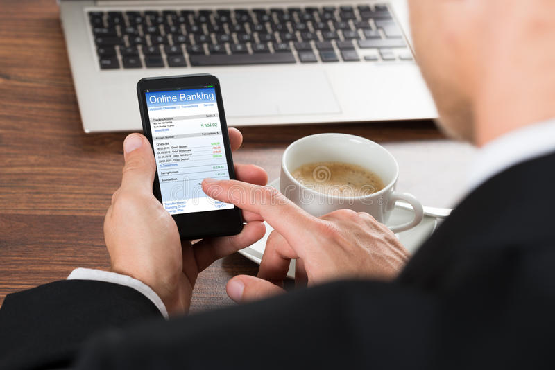 Geschäftsmann unter Verwendung des Online-Bankings-Services am Mobiltelefon lizenzfreies stockfoto