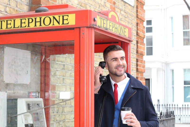 Geschäftsmann unter Verwendung einer roten Telefonzelle lizenzfreie stockfotos