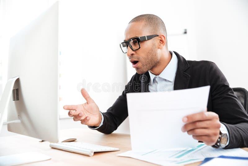 Geschäftsmann unter Verwendung eines Laptops und des Schauens entsetzt lizenzfreies stockfoto
