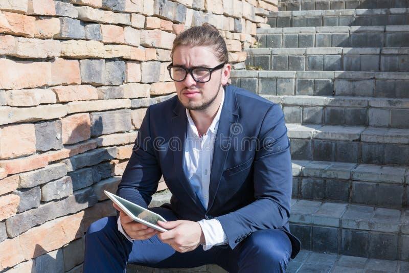 Geschäftsmann unter Verwendung eines Tabletten-PC auf einer Stadtstraße lizenzfreies stockbild
