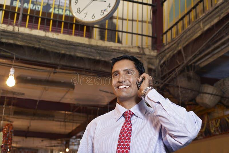 Geschäftsmann Using Cell Phone im Basar lizenzfreie stockfotos