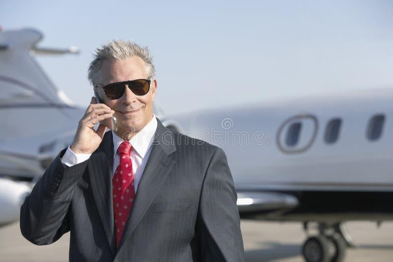Geschäftsmann Using Cell Phone mit privater Jet In Background lizenzfreie stockbilder
