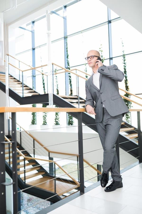 Geschäftsmann Using Smartphone While, das auf Geländer sich lehnt stockbild