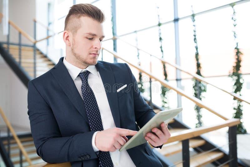Geschäftsmann Using Tablet Computer beim Lehnen auf dem Mit der Eisenbahn befördern lizenzfreies stockbild