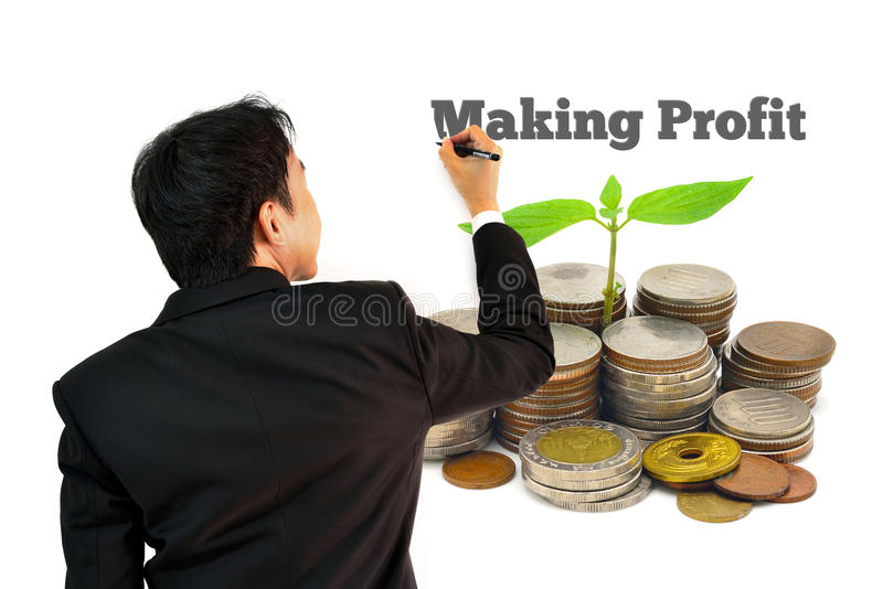 Geschäftsmann von der Rückseite, schreibend, Gewinn auf Stapel Münzen mit dem wachsenden Sprössling erzielend lokalisiert auf wei lizenzfreie stockfotos