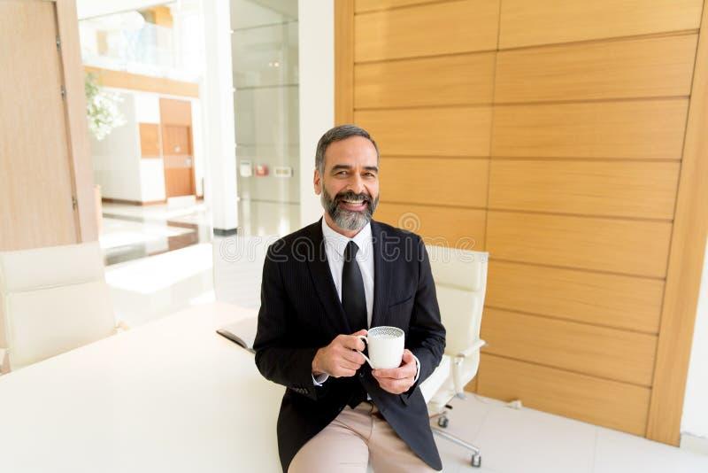 Geschäftsmann von mittlerem Alter, der coffe Bruch im modernen Büro hat lizenzfreie stockbilder