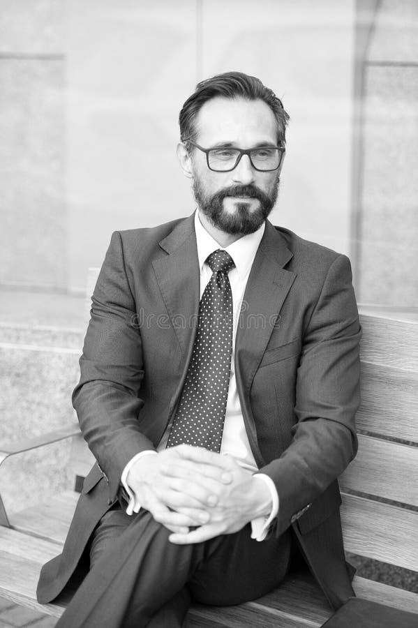 Geschäftsmann von mittlerem Alter, der entspannende Pause auf Bank macht Stadt-Leben-Reihe Geschäftspersonen Porträt des Geschäft stockfotografie