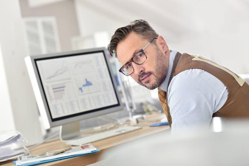 Geschäftsmann von mittlerem Alter, der an Statistiken arbeitet lizenzfreie stockbilder
