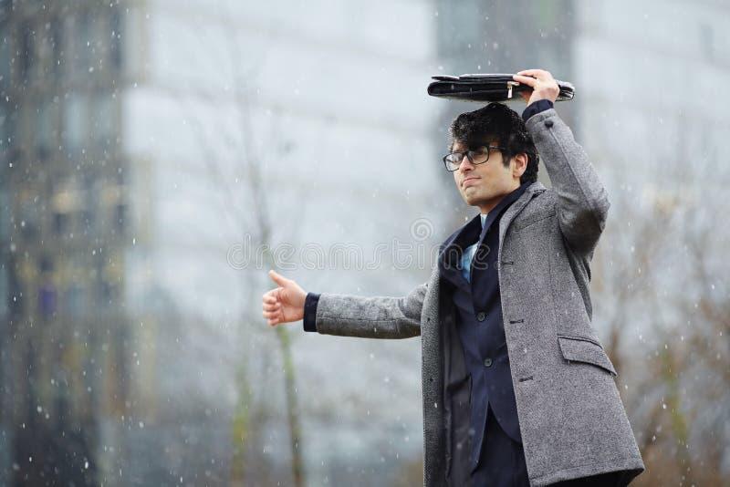 Geschäftsmann Waiting für Taxi im Schnee stockfoto