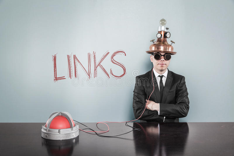 Geschäftsmann Wearing Helmet Sitting durch Link-Text auf Gray Wall lizenzfreie stockbilder