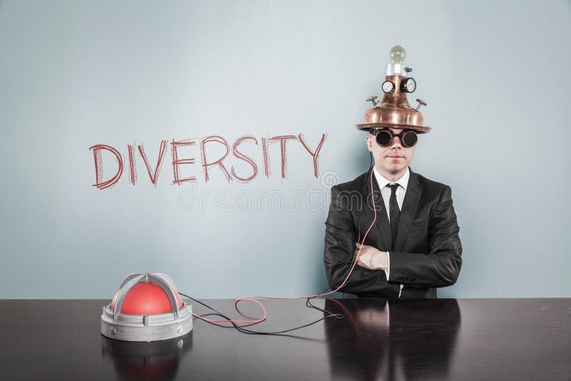 Geschäftsmann Wearing Helmet Sitting durch Verschiedenartigkeits-Text auf Gray Wall stockfotografie