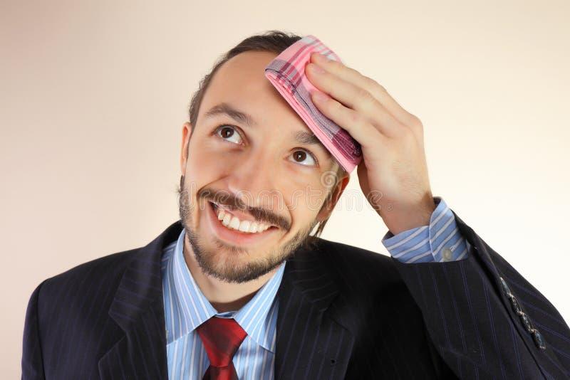Geschäftsmann wischt eine Stirn durch Halstuch ab stockfotografie