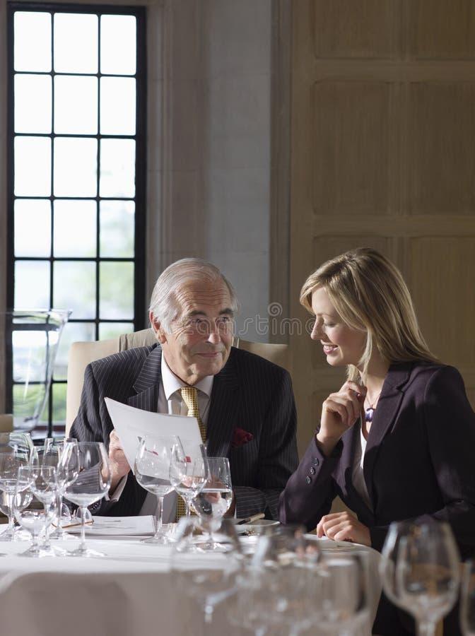 Geschäftsmann-And Woman Reading-Dokumente am Restaurant-Tisch lizenzfreie stockfotos