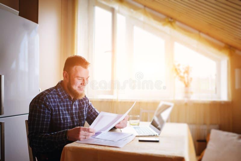 Geschäftsmann zu Hause, arbeitet er mit einem Laptop und überprüft Schreibarbeit und Rechnungen stockfotografie