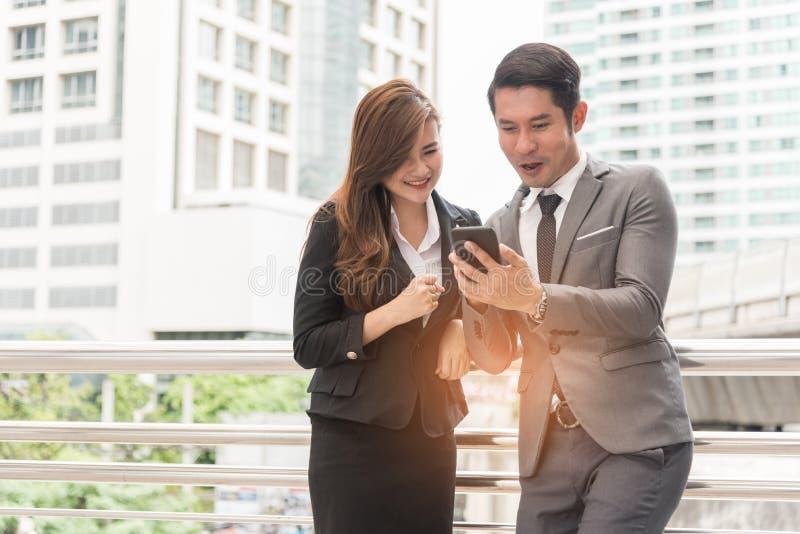 Geschäftsmann zwei und Frau genießen, Handy zu verwenden Entspannen Sie sich Zeit und Glückkonzept lizenzfreie stockbilder