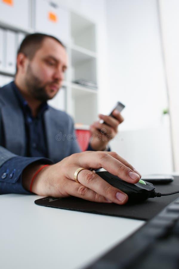 Geschäftsmannarbeit über Computergriffmaus im Arm und im Handy in anderer Nahaufnahme stockbilder