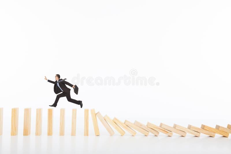 Geschäftsmannbetrieb und Fangen auf dem Stürzen von Dominos stockfotografie