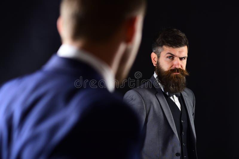 Geschäftsmannblick auf einander mit Urteil Blickkontaktkonzept Teilhaber auf ernsten Gesichtern stehen gegenüber von lizenzfreies stockfoto