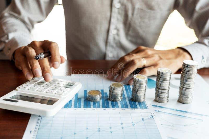 Geschäftsmannbuchhalter Calculating auf Datendokumenten und Stapel Stapel Münzen, die Einsparungensgeldanlage Finanzbudget lizenzfreies stockfoto
