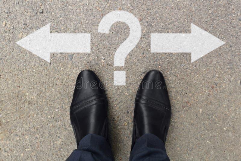 Geschäftsmannfüße in den Schuhen, die auf Asphaltfahrbahnmarkierungen mit dem Pfeilzeigen link und recht mit Fragezeichen stehen  stockbilder