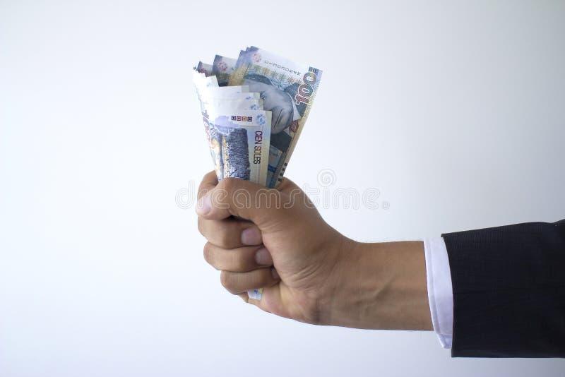 Geschäftsmannfaust, die 100 Sohlenrechnungen, peruanisches Währungskonzept hält stockfotografie