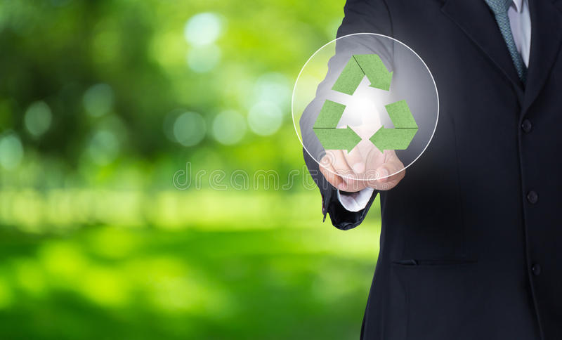 Geschäftsmannfinger, der auf grünes PapierRecycling-Symbol mit Naturhintergrund zeigt lizenzfreie stockbilder