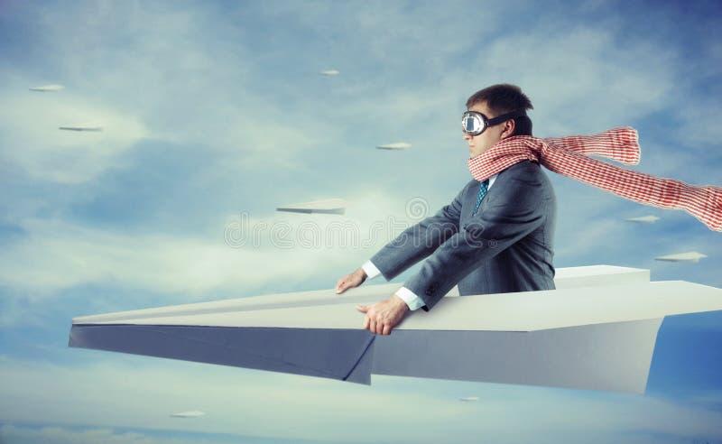 Geschäftsmannfliegen auf Papierflugzeug stockfotografie