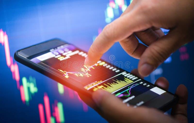 Geschäftsmanngebrauch Smartphone, der in der Hand die on-line-Devisen oder Devisenmarktbrettdatenschirm auf Lager beweglich hande stockfoto