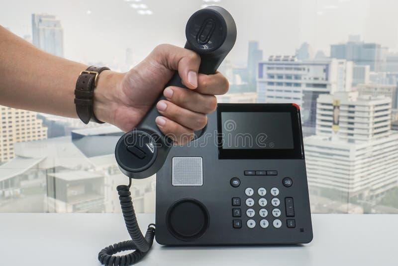 Geschäftsmanngriffkopfhörer von Büro IP-Telefon für Kommunikation und Marketing lizenzfreie stockfotografie