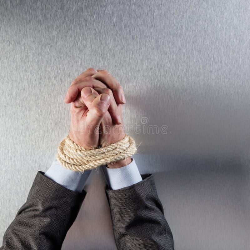 Geschäftsmannhände gebunden mit dem Seil, das für Angestelltfrieden betet stockfotografie