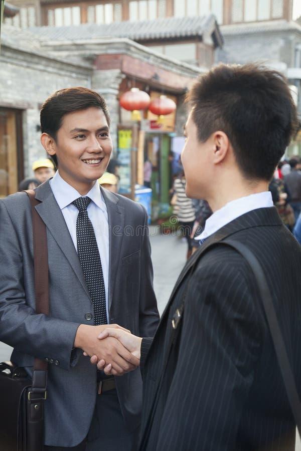 Geschäftsmannhändeschütteln mit zwei Jungen im houhai, Peking, China stockfotos