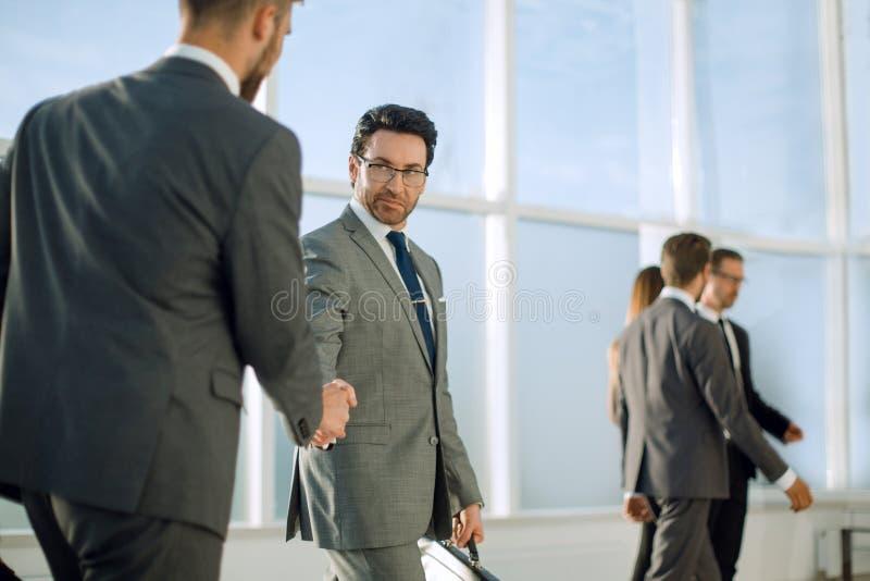 Geschäftsmannhändeschütteln nach auffallendem Abkommen stockbild