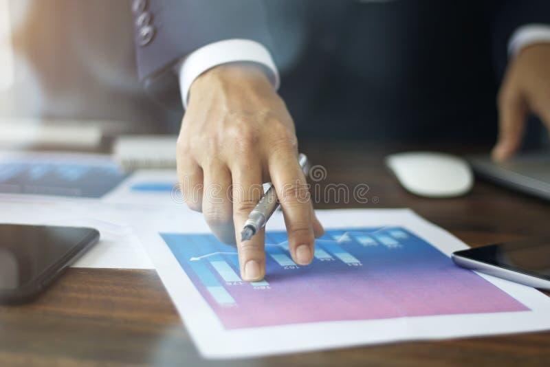 Geschäftsmannhand, die auf Diagrammdiagrammwachstums-Geschäftsdokument zeigt stockbilder